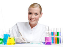 Female doctor makes some notes. Female doctor surrounded by medical glassware makes some notes, isolated on white Royalty Free Stock Photos