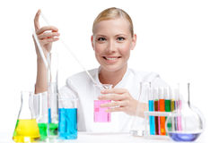 Female doctor makes some researches. Female doctor surrounded by medical vials and flasks makes some researches, isolated on white Stock Images