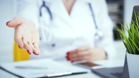 Female doctor making welcome gesture, politely inviting patient to sit down in medical office. Photo with depth of field. Female doctor making welcome gesture Royalty Free Stock Images