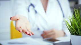 Female doctor making welcome gesture, politely inviting patient to sit down in medical office Фото с глубиной поля стоковое изображение