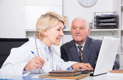 Female doctor with male client. Old male visitor consulting smiling aged women doctor in hospital Royalty Free Stock Image