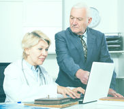 Female doctor with male client. Old male visitor consulting smiling aged women doctor in hospital Royalty Free Stock Photos
