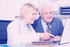Female doctor with male client. Old male visitor consulting smiling aged women doctor in hospital Royalty Free Stock Images