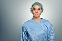 Female doctor or male nurse in scrubs. Attractive middle-aged female doctor or nurse in scrubs and a sterility cap looking directly at the camera over a grey Stock Image