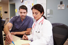Female Doctor With Male Nurse Working At Nurses Station Royalty Free Stock Images