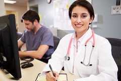 Female Doctor With Male Nurse Working At Nurses Station. Smiling To Camera Royalty Free Stock Images