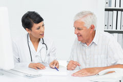 Female doctor with male patient reading reports Stock Photography