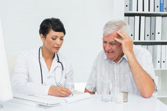 Female doctor with male patient reading reports Stock Photo