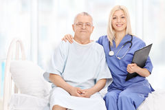 Female doctor and a mature patient seated on bed Royalty Free Stock Photography