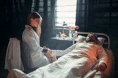 Female doctor measures the pulse of sick man Royalty Free Stock Photos