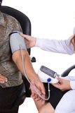 Female doctor measuring blood pressure of senior woman Stock Image