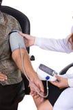 Female doctor measuring blood pressure of senior woman Stock Image