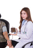 Female doctor measuring blood pressure of senior woman Royalty Free Stock Photo