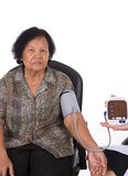 Female doctor measuring blood pressure of senior woman Stock Photography