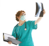 Female doctor in medical mask looking at x-ray Royalty Free Stock Images