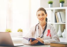 Female doctor in medical office. Pink ribbon for breast cancer awareness. Female doctor in medical office. Raising knowledge people living with tumor illness stock images