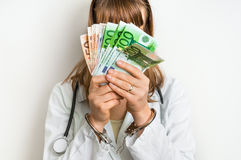 Female doctor with money and handcuffs - bribe concept. Female doctor with money and handcuffs - corruption and bribe concept in medicine Stock Image