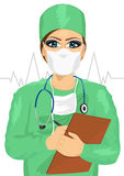 Female doctor or nurse in face mask taking notes Royalty Free Stock Image