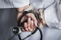 Female Doctor or Nurse In Handcuffs Holding Stethoscope Stock Photo