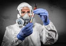 Female Doctor or Nurse In Hazmat Gear Holding Positive Coronavirus Test Tube