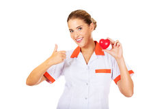 Female doctor or nurse holding toy heart and shows thumb up Stock Images