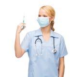 Female doctor or nurse in mask holding syringe Stock Image