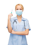 Female doctor or nurse in mask holding syringe Royalty Free Stock Images