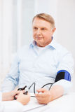Female doctor or nurse measuring blood pressure Royalty Free Stock Images