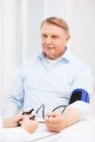 Female doctor or nurse measuring blood pressure. Healthcare, elderly and medical concept - female doctor or nurse with male patient measuring blood pressure Royalty Free Stock Images
