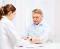 Female doctor or nurse measuring blood pressure. Healthcare, elderly and medical concept - female doctor or nurse with male patient measuring blood pressure Stock Image