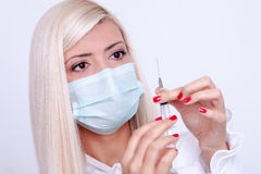 Female doctor or nurse in medical mask holding syringe with inje Royalty Free Stock Photography