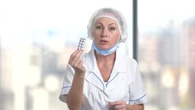 Female doctor nurse prescribing pills. Bright blurred background stock video footage