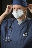 Female Doctor or Nurse Putting on Protective Face Mask Royalty Free Stock Images