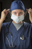 Female Doctor or Nurse Putting on Protective Face Mask Royalty Free Stock Photos