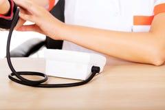 Female doctor or nurse sitting behind the desk holding blood pressure gauge Royalty Free Stock Photos