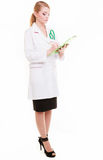 Female doctor or nurse with stethoscope writing with pen on clipboard. Stock Photography