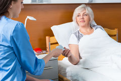 Female doctor or nurse in uniform is giving pills to her patient Royalty Free Stock Images