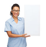 Female doctor or nurse with white blank board. Healthcare, advertisement and medicine concept - smiling female african american doctor or nurse in eyeglasses Royalty Free Stock Images