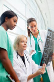 Female doctor and nurses look at CT scan Royalty Free Stock Images
