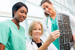 Female doctor and nurses look at CT scan Stock Images