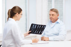 Female doctor with old man looking at x-ray Royalty Free Stock Image