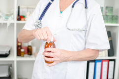 Female doctor opening a syrup bottle Stock Image