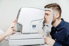 Female doctor ophthalmologist clinic checks eye vision of man on machine lamp. Concept diagnostic glasses and lenses royalty free stock images