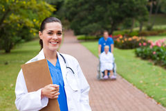 Female doctor outdoors. Friendly female doctor portrait outdoors, background is her colleague pushing patient in wheelchair Stock Image