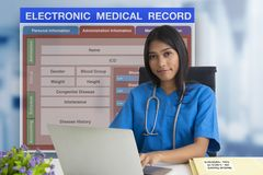 Female doctor with patient blank form of electronic medicale record system on background stock images