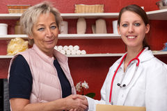 Female doctor and patient with handshake. Young female doctor ist giving a aged patient a handshake, red office in the background, both are smiling Royalty Free Stock Images