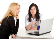 Female doctor with patient looking at laptop Stock Photos