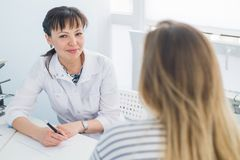 Female doctor and patient talking in hospital office. Health care and client service in medicine royalty free stock images