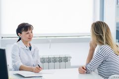 Female doctor and patient talking in hospital office. Health care and client service in medicine stock images