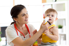 Female doctor pediatrician using nasal aspiration for child. Mucus suction patient kid baby. Royalty Free Stock Photo